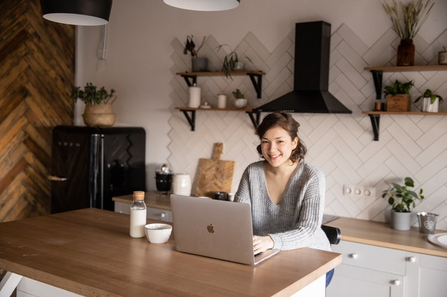 A woman in a kitchen smiling at her laptop as she uses digital currency as the future of Internet shopping.