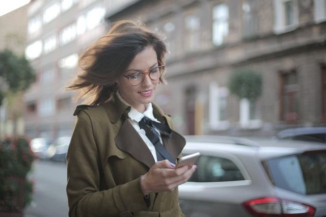 A woman walking with her ride-hailing app open on her phone.