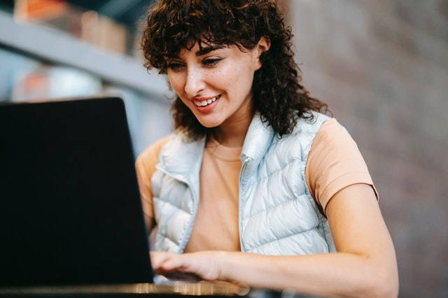 A woman smiling at her laptop as she orders a product with online delivery services.