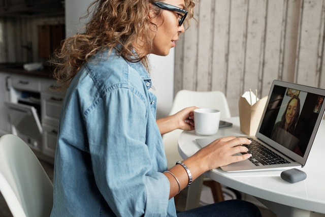 A woman with a cup of tea and a laptop on a video call on Zoom using practices to avoid Zoombombers.