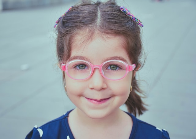 A girl smiling wearing pink baby glasses bought online.