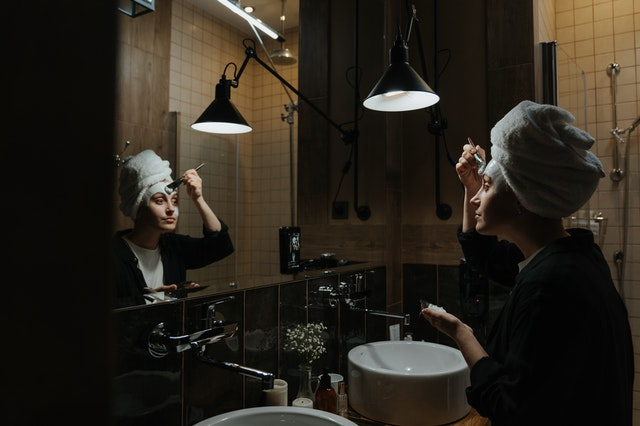 A woman with a towel on her head applying products in the mirror to look and feel younger.