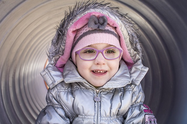 A girl wearing glasses bought online with a kids glasses case smiling.