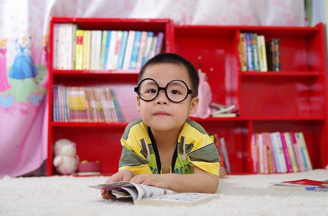 A child wearing kids glasses online lying on the floor reading a book.