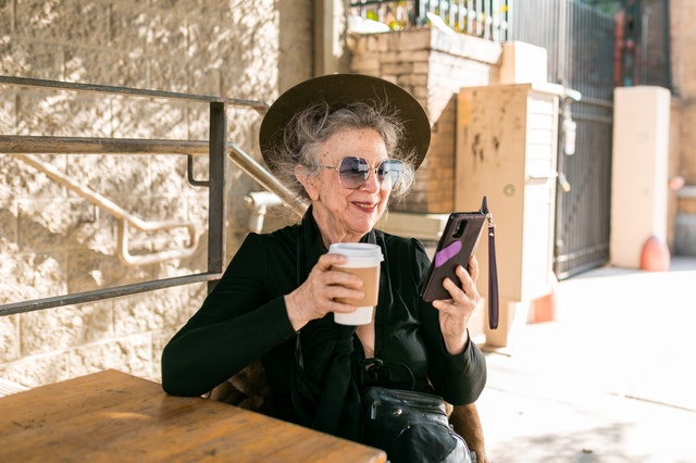 A woman looking at her phone and holding a coffee looking and feeling younger.