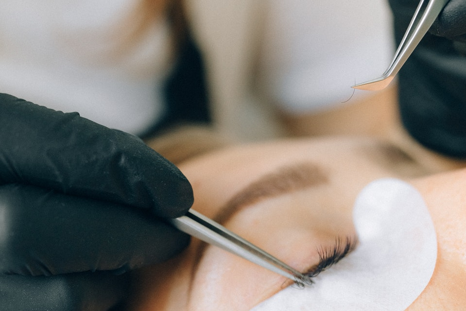 A woman with undereye pads on getting eyelash extensions from a beauty professional with gloves and tweezers.