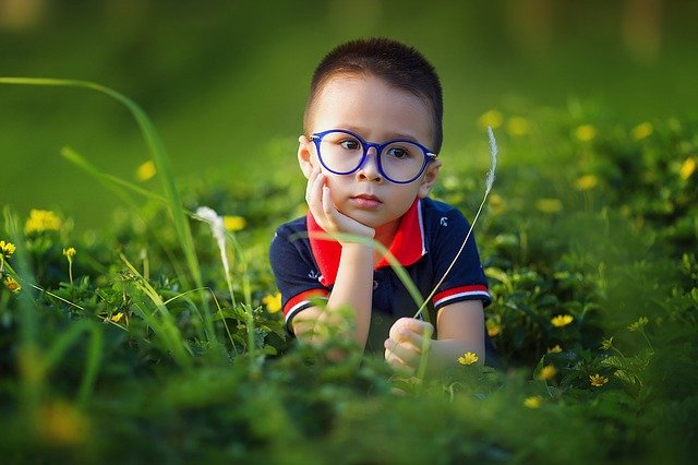 A child sitting in a field wearing unbreakable glasses for kids.