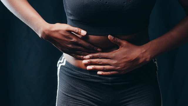 A woman standing holding her stomach because she has abdominal muscle separation.