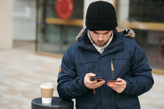 A man with a phone, coffee and credit care seeing a cybersecurity threat on his bank account.