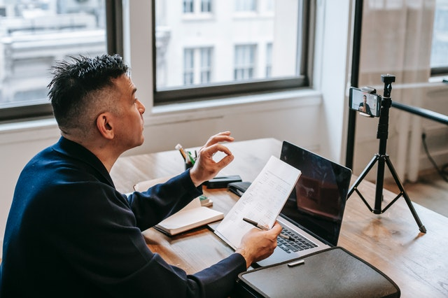 A man using an e-learning app for his business. He is holding a notebook and speaking to a laptop.