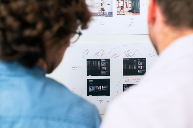 Two people looking at a board with a plan for designing a good business app.
