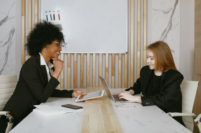 Two women from an SEO company talking and using their laptops to work.
