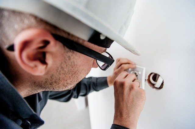 An electrician checking sockets due to homeowner local electrical emergency.