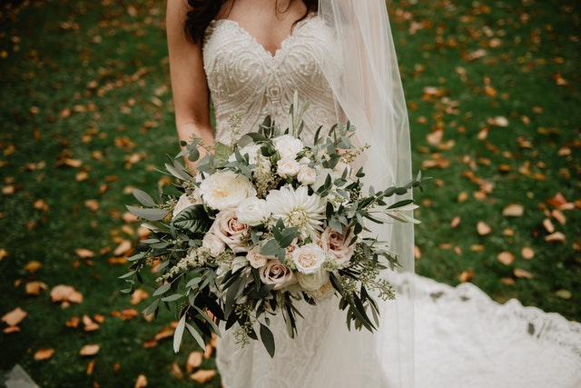 A bride at her planned outdoor pandemic wedding holding flowers during lockdown.