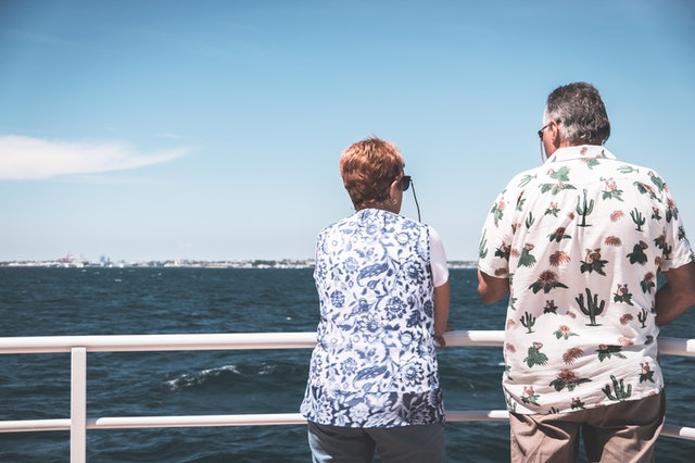 A man and a woman looking out at a port from the railing of their 2022 Australian cruise ship.