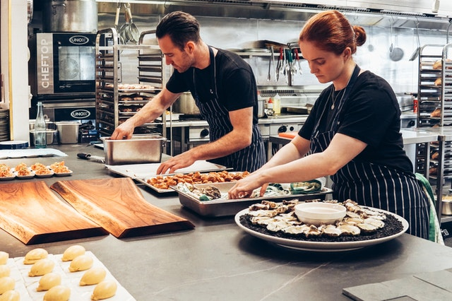 Two chefs cooking food in the kitchen in the food industry trends and forecasts.