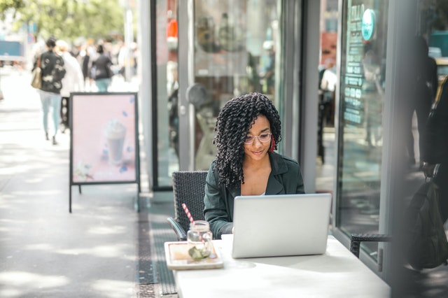 A woman at a cafe working as a part time blogger.