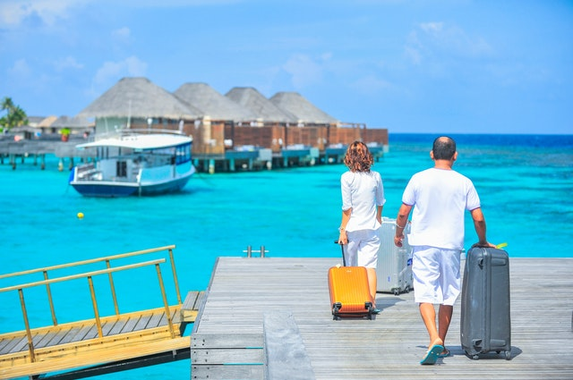 A couple with suitcases walking towards the ocean after planning their summer vacation.