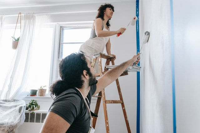 A couple painting their new Sydney apartment that they have developed.