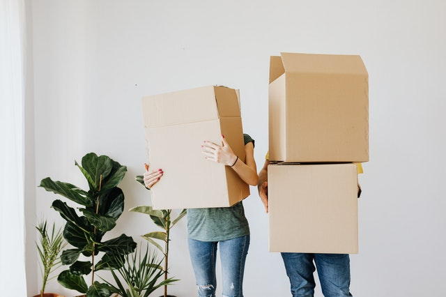 A couple holding boxes for their new Sydney property development home.