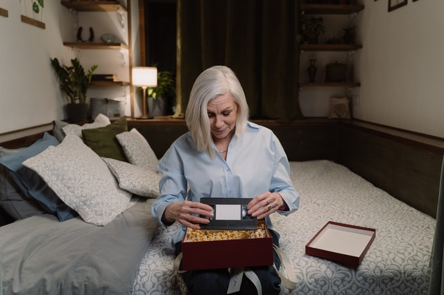 A woman sitting on a bed rescuing her tangled memories pulling a VHS out of a box.