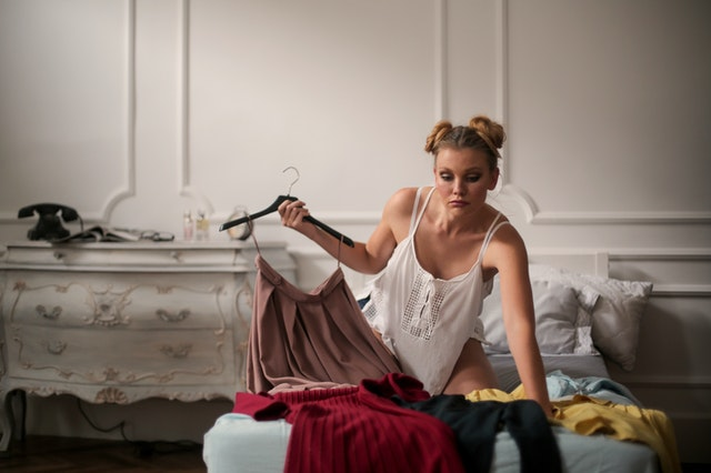 A woman sorting through and caring for her clothing to reduce her fashion waste and carbon footprint.