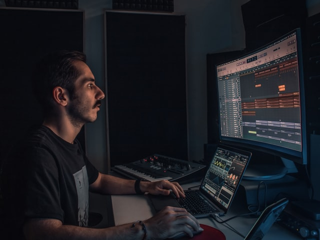 A man sitting at the computer in his home studio set up for making hit songs.