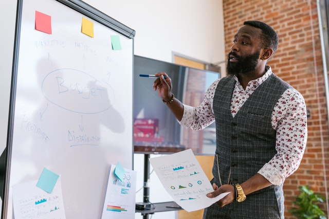 A man using a whiteboard to plan digital marketing strategy and avoid mistakes.
