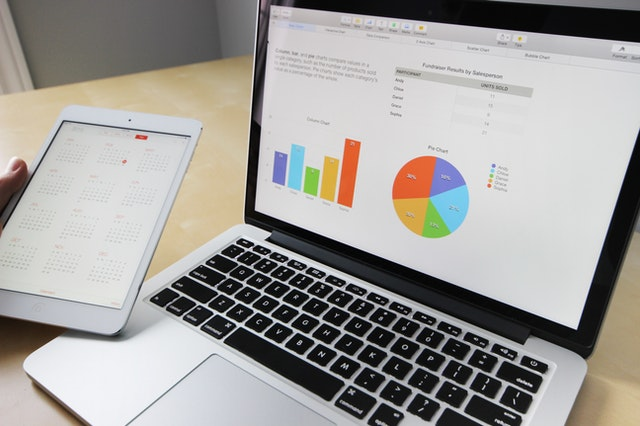 A laptop and tablet with digital marketing statistics and mistakes to avoid.
