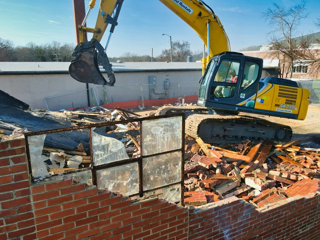 A digger machine renovating a home by safely practicing demolition.