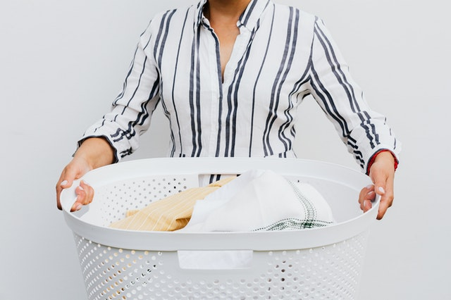 A woman holding a laundry basket of clothing for reducing fashion waste and carbon footprint.