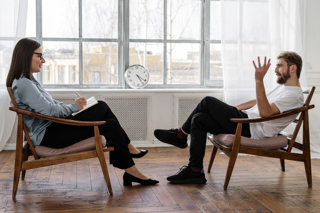 A therapist talking to a man about managing back to work anxiety.