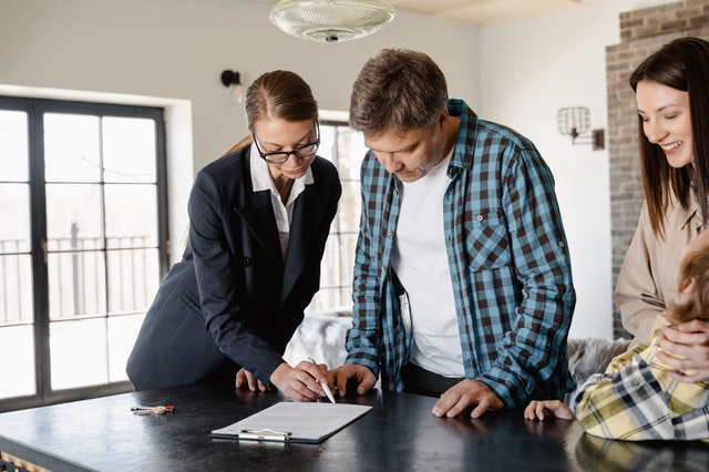 A real estate professional helping a couple sign a mortgage and buy a new home.