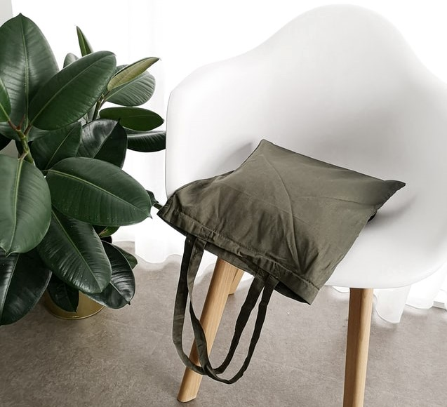A green canvas tote shopping bag on a white chair with a plant.