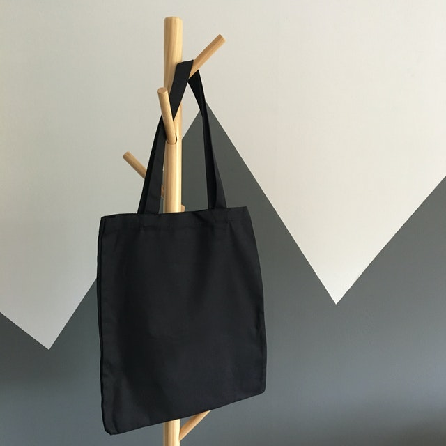 A black recyclable canvas tote bag with many benefits for shopping hanging on a coat hanger.