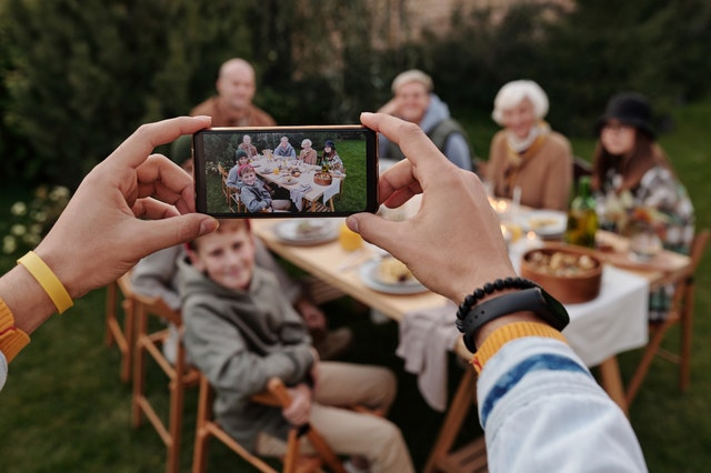 Someone using tips and tricks to take an awesome photo of a family at a table on their phone.
