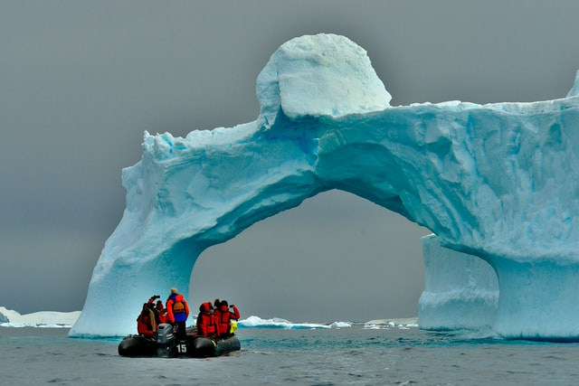 People travelling on a boat under an iceberg in Antarctica as a wild travel trend.