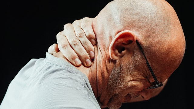 A man with his hand on his neck to get back pain relief.