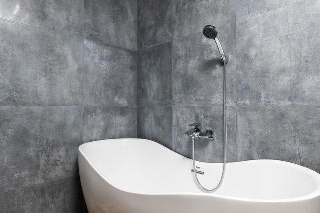 A bathtub with laid tiles around it.