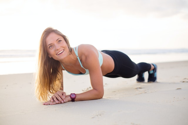 Beach health as a lady gets benefits from planking.