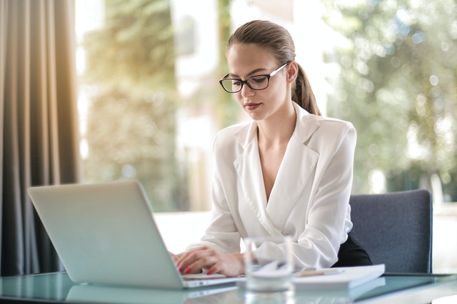 A woman looking at her laptop as she works at her dream job due to coaching from a corporate career company.