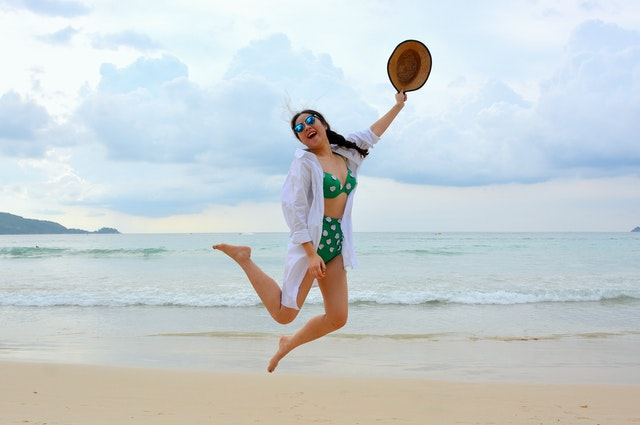 A woman in a high waisted thong bikini jumping in the air on a beach because she checked the online returns policy.