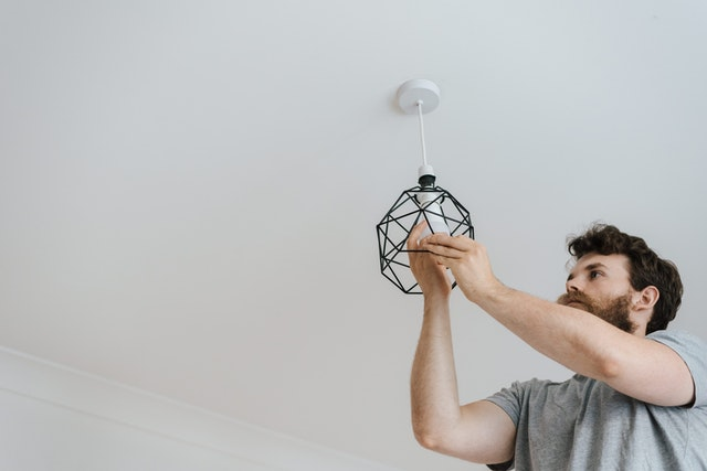 A man changing a light to reduce his electricity bill this winter.