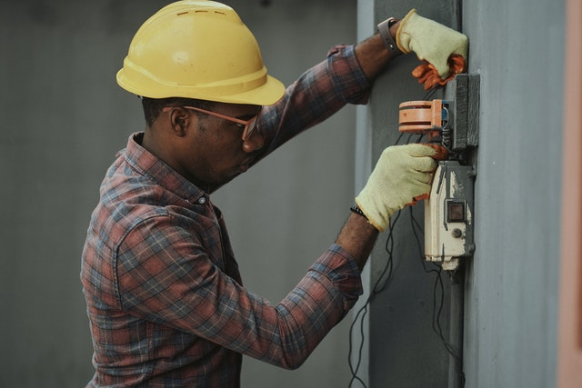 An electrician fixing a box to reduce a winter electricity bill.