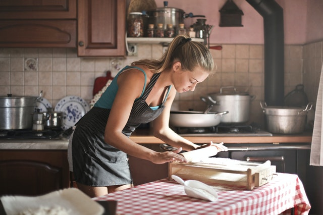 A woman in a kitchen making food from a food blog.