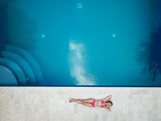 A woman in a high waisted thong bikini with a returns policy next to a pool.