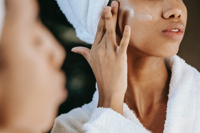 A woman putting moisturiser on her skin as part of her business meeting hair and makeup routine.