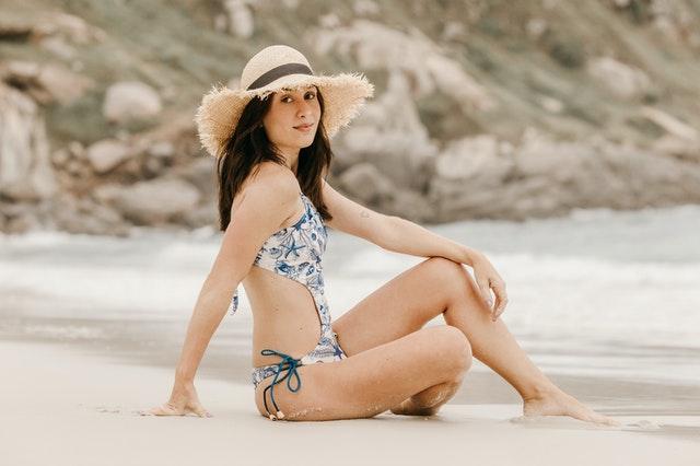Woman with Myra Swim brand enjoying beach.