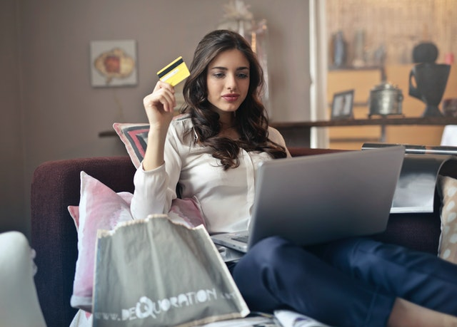 A woman on her laptop with a credit card browsing an online retail store that has been effected by second wave covid.