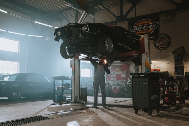 A man in a repair shop under a suspended car that he is selling auto parts of online.